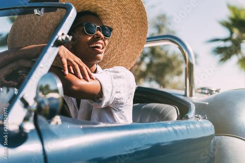 Black woman driving a vintage convertible car - 233424977