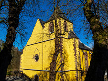 Castle Church Of St. Philip And St. James In Schleiden, North Rhine-Westphalia Germany, Exterior Side View Through April Tree Branches