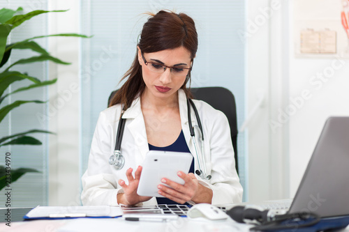 Beautiful female doctor in her studio using a digital tablet