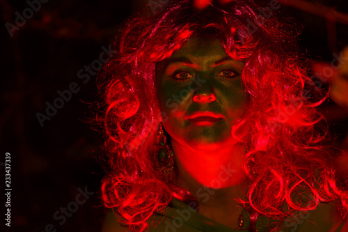 Foto op Aluminium Carnaval The face of the woman of the forest witch is a close-up in the gleam of red light. Light falls on the face.