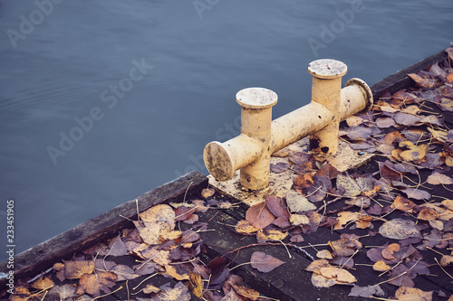 Fotografía  Old mooring bollard in a marina covered with autumnal leaves, color toned picture