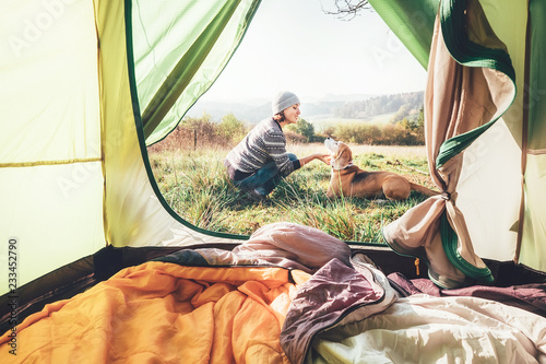 Poster de jardin Camping Woman pand her dog tender scene near the camping tent. Active leisure, traveling with pet concept image