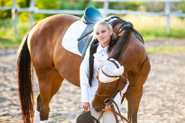 Fototapeta Girl equestrian rider stands near the horse. Horse farm. Horse theme