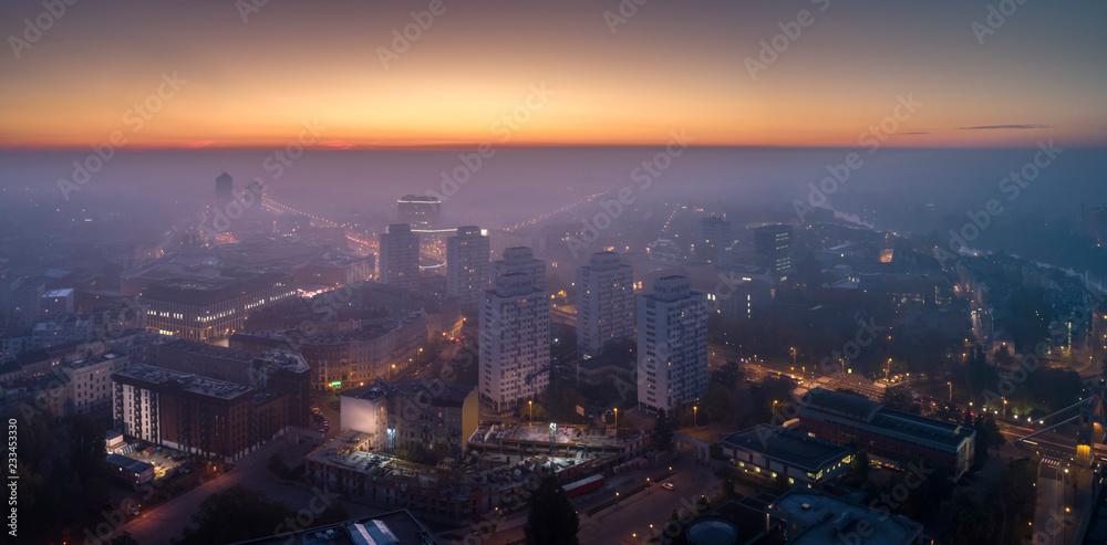 Fototapeta Widok z lotu ptaka na smog nad budzącym się miastem o świcie, budynki okryte mgłą i smogiem - Wrocław, Polska