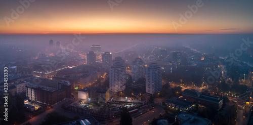Widok z lotu ptaka na smog nad budzącym się miastem o świcie, budynki okryte mgł Fototapeta