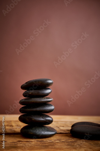 Spoed Foto op Canvas Spa stack of black spa stones for massage on a brown background and an old wooden table