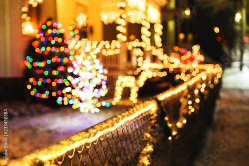 shiny Christmas decorations outside at night. blurred background city street with Christmas illuminations. Cope