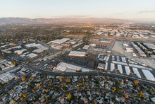 Late Afternoon Aerial View Of Homes, Industrial Buildings, Tarmac And Runway At Van Nuys Airport In The San Fernando Valley.