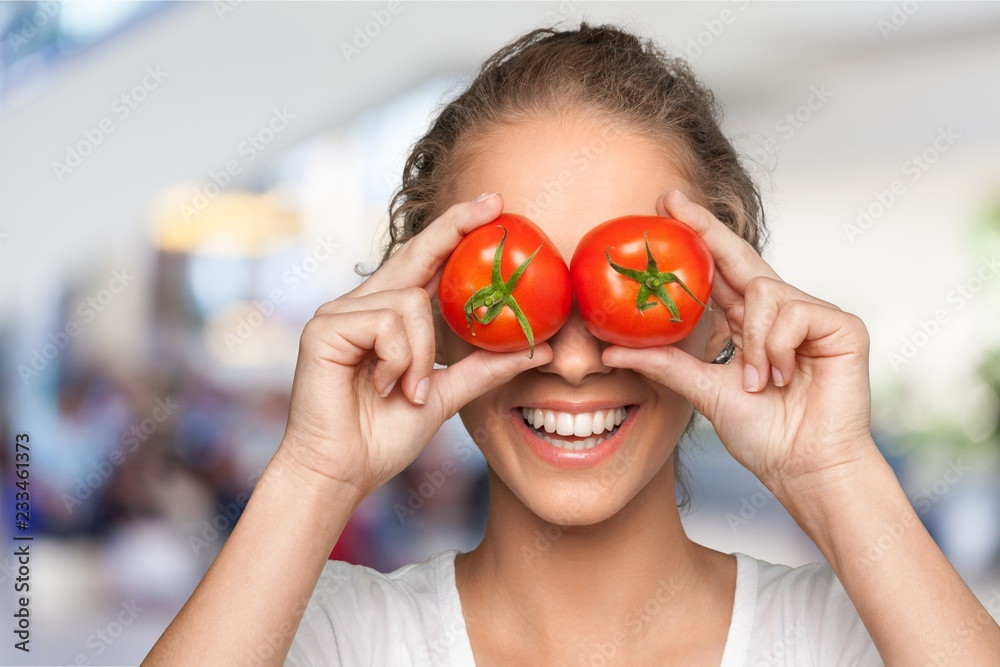Fototapety, obrazy: Beautiful laughing woman holding two ripe tomatoes before her