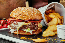 Big Burger With Juicy Cutlet, Cheese, Tomato, Lettuce, Served With French Fries And Barbecue Sauce On A Black Plate On The Background Of Copper Plates. Close Up
