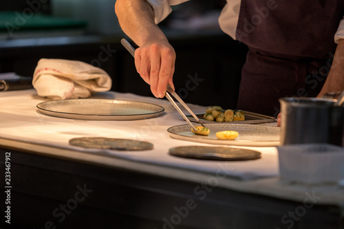 Chef preparing an entree in the kitchen of a restaurant Canvas Print