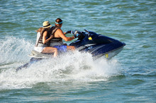 Young Couple Riding Waves In T...