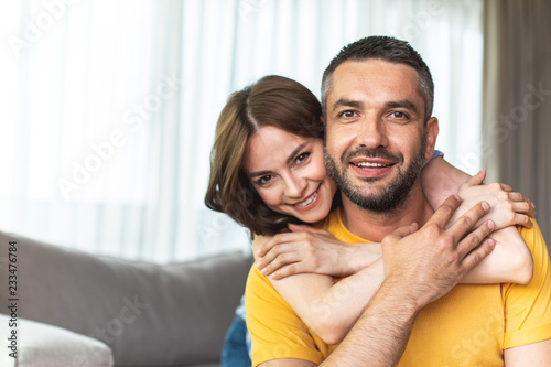 Canvas Print Beautiful young couple is sitting in room at home while smiling
