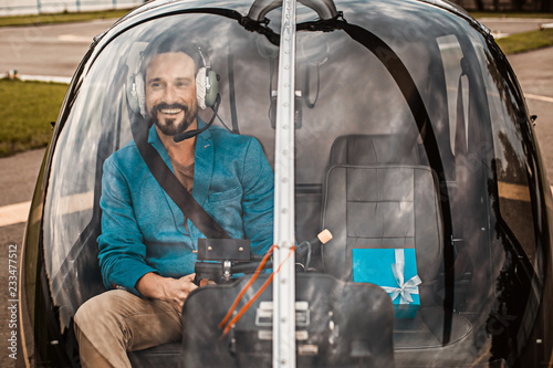 Cheerful bearded young man enjoying being in the helicopter cabin and smiling while having beautiful present next to him