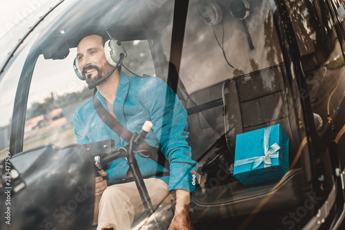 Cheerful bearded young man sitting with lovely present in the helicopter cabin and smiling