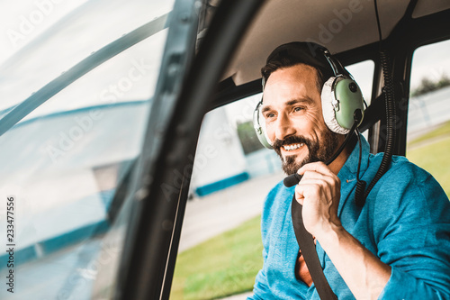 Cheerful relaxed man in big headphones smiling while sitting in the helicopter cabin