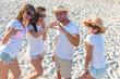 Cuatro amigoss sexys de blanco en la playa sobre la arena riendo y haciendo selfies.