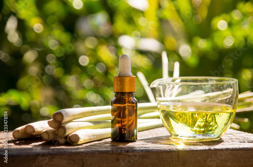Fotografie, Obraz  Lemongrass essential oil is placed on the table using a hand-drip oil lemongrass oil - spa and insect repellent