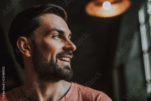 Fotografie, Obraz  Side view beaming unshaven male looking away while locating indoor