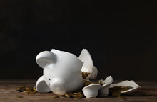 Broken Piggy Bank With Money On Table Against Dark Background