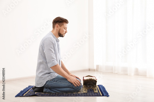 Muslim man with Koran praying on rug indoors. Space for text