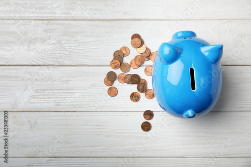 Fotografía  Cute piggy bank and coins on wooden background, top view with space for text