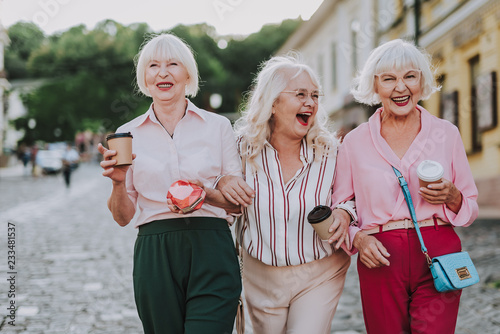 Waist up photo of three females with cardboard glasses in hands. White-haired old ladies alking together