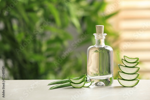 Bottle with aloe vera juice and slices of fresh leaves on table against blurred background. Space for text