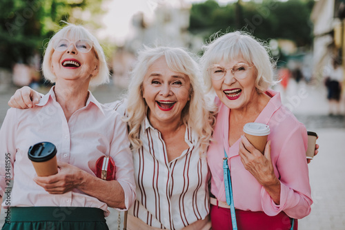 Photo Waist up portrait of three laughing grannies walking around the city while holdi