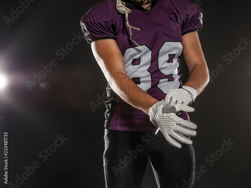 American football player wearing uniform on dark background, closeup