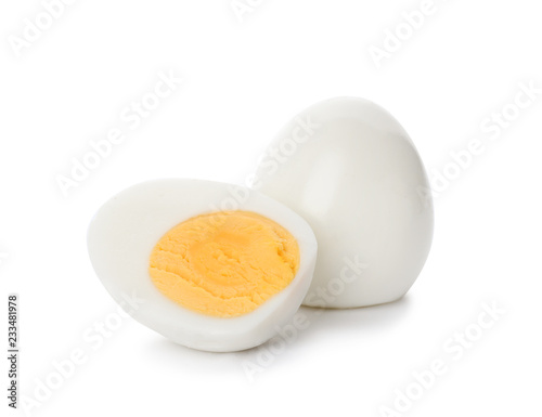 Photo Sliced and whole hard boiled eggs on white background