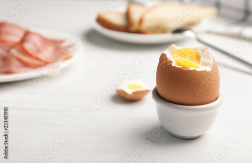 Holder with soft boiled egg on table. Space for text