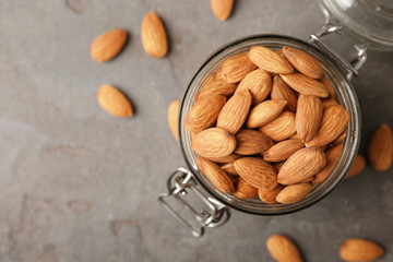 Fototapeta Tasty organic almond nuts in jar and space for text on table, top view