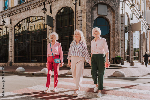 Fotografía  Full-length photo of three modern older ladies are crossing road while happily l
