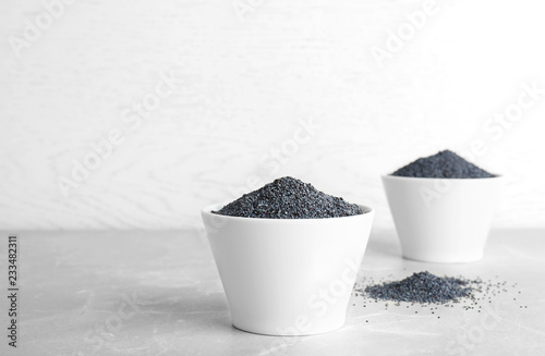 Foto op Canvas Aromatische Poppy seeds in bowl on table against light background. Space for text
