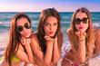 Tres bellas y picaras mujeres muy sexys lanzando besos sobre la arena de una playa del caribe.