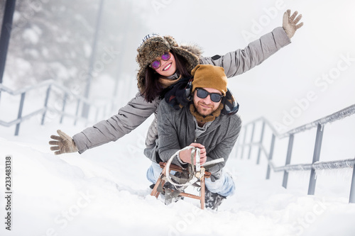 Obraz Young happy couple riding sled in snow - fototapety do salonu