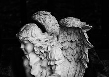 Black And White Image Of An Angel Statue In A Cemetery.
