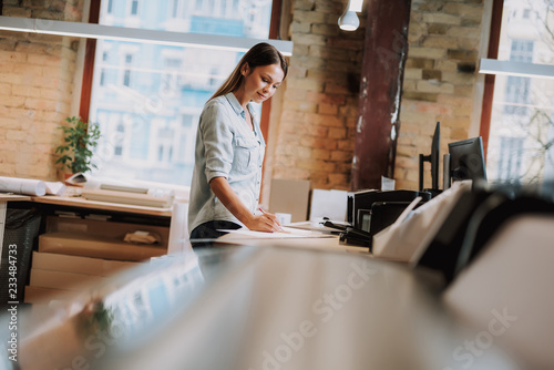 Valokuva  Side view portrait of charming girl in blue shirt making notes while standing ne