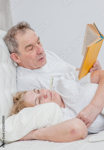 Fotografia  elderly man reading a book to his ill wife