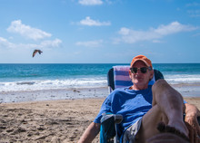 Handsome Older Baby Boomer Man Wearing An Orange Cap Sitting On Beach Chair By The Ocean With A Serious Look On His Face.