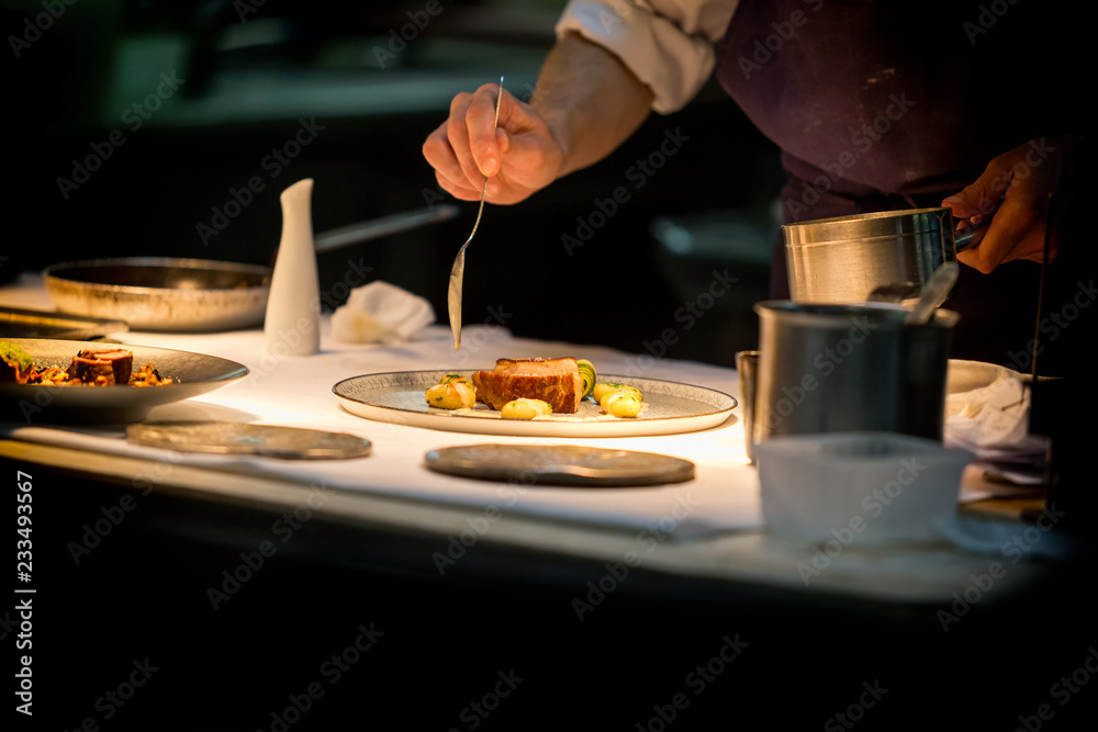 Fotografía Chef preparing a dish with meat on a plate under a light