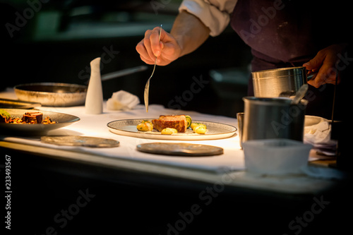 Fototapeta Chef preparing a dish with meat on a plate under a light. The chef is meticulous.  obraz