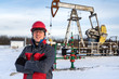 Man worker in the oilfield near pump jack and wellhead, wearing helmet and work clothes. Industrial site background. Oil and gas concept.