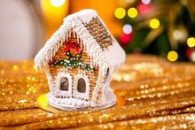 Gingerbread House In Front Of Defocused Lights Of Christmas Decorated Fir Tree. Holiday Sweets. New Year And Christmas Theme. Festive Mood. Christmas Card