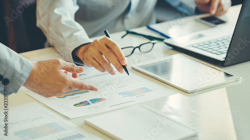 Fotografie, Obraz  Two businessman investment consultant analyzing company financial report balance sheet statement working with documents graphs