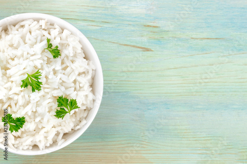 A closeup photo of a bowl of cooked white long rice, shot from above on a teal blue background with a place for text