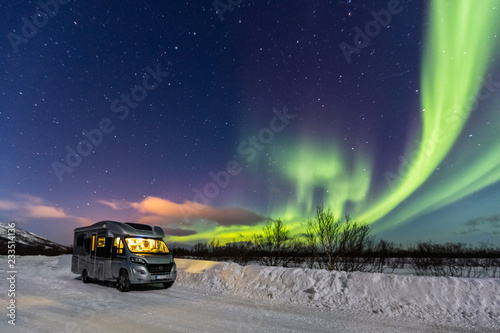 Fotografie, Obraz Beautiful green northern lights and camper with light