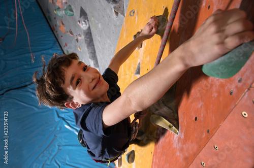Fotografie, Obraz little boy climbing a rock wall