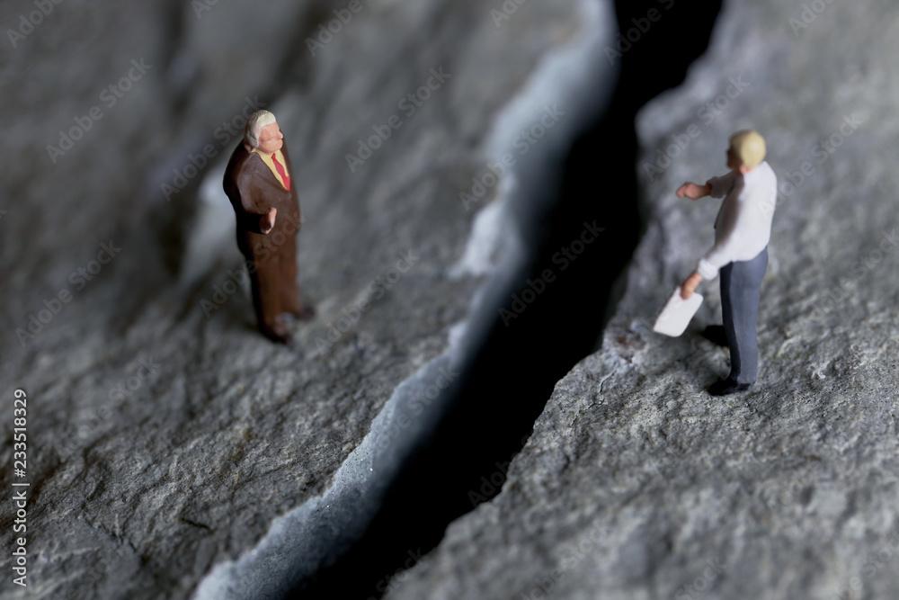 Fototapeta 岩の亀裂と交渉するビジネスマンたち